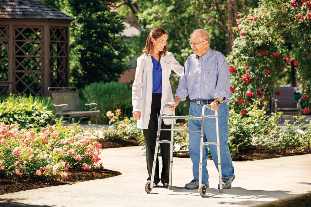 FSL employee assisting a gentleman using a walker